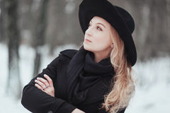 Woman winter snow nature portrait in black coat and hat.  Royalty Free Stock Photos
