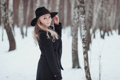 Woman winter snow nature portrait in black coat and hat.  Royalty Free Stock Images