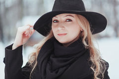 Woman winter snow nature portrait in black coat and hat.  Stock Photos