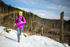 Woman winter trail running in mountains on snow Stock Images