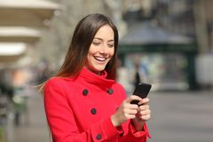 Woman in winter walks and uses smart phone. Happy woman wearing red jacket in winter walks and uses smart phone in the street royalty free stock photos