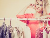 Woman in winter wardrobe deciding what wear. Woman standing in wardrobe with winter clothes, can not decide what to wear. Picking winter clothing concept Royalty Free Stock Photography