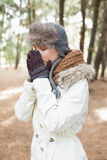 Woman in winter wear sneezing in woods Stock Photos