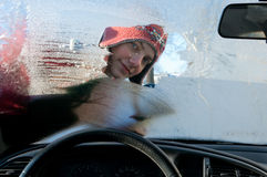 Woman winter windshield. Young woman cleaning windshield from snow and ice in winter stock image