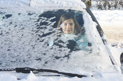 Woman winter windshield. Young woman behind windshield with snow and ice in winter royalty free stock photo