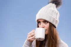 Woman in winter wool cap drinking tea Royalty Free Stock Photos