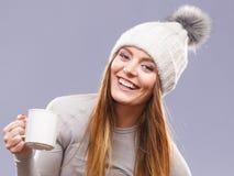 Woman in winter wool cap drinking tea Stock Images
