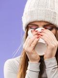 Woman in winter wool cap drinking tea Royalty Free Stock Image
