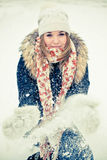 Woman in wintry coat. Attractive young woman in wintry coat with large fur head, snowy in background Stock Image