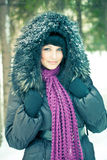 Woman in wintry coat. Attractive young woman in wintry coat with large fur head, snowy forest in background Stock Photo