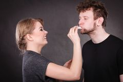 Woman wipe man face by hygienic tissue. Hygiene and skincare concept. Protection and help in relationship. Smiling happy women wipe cream face nose of funny men royalty free stock images
