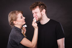 Woman wipe man face by hygienic tissue. Royalty Free Stock Photography