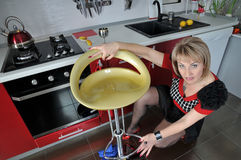 The woman wipes a dust on kitchen. Royalty Free Stock Photography