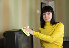 Woman wipes the dust  on TV Stock Image