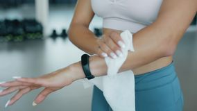 Woman wipes hands with a wet napkin in a fitness center. Woman wipes her hands with a wet napkin in a fitness center stock video