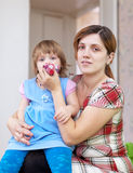 Woman wipes snot  child at home Royalty Free Stock Photography