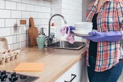 Woman wiping clean plate with towel in the kitchen. Royalty Free Stock Images