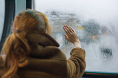 Woman wiping dew off window. A young woman is wiping the dew off a window in a bus Stock Photos