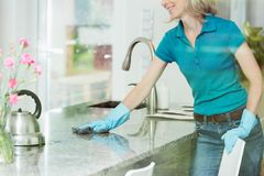 Woman wiping down kitchen countertop stock image