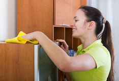 Woman wiping the dust from furniture Royalty Free Stock Photography