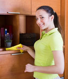 Woman wiping the dust from furniture Stock Image