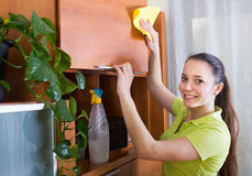 Woman wiping the dust from furniture Stock Photos