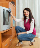 Woman wiping the dust on TV Royalty Free Stock Images