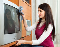 Woman wiping the dust on TV in living room Stock Photography