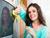Woman wiping dust on TV Royalty Free Stock Image