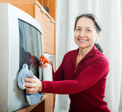 Woman wiping the dust  on TV Stock Photos