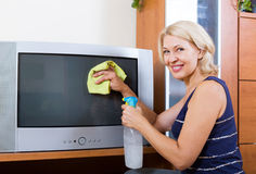 Woman wiping the dust TV Royalty Free Stock Photography