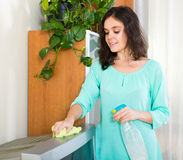 Woman wiping dust on TV Stock Photo
