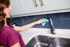 Woman wiping faucet at kitchen sink Stock Photos