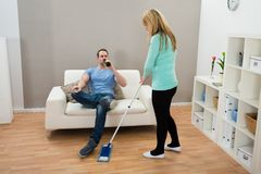 Woman wiping floor while man drinking alcohol Royalty Free Stock Photo