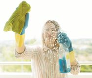 Woman is wiping glass. House cleaning. Woman is wiping glass on the balcony Stock Images