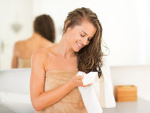 Woman wiping hair with towel in bathroom. Happy young woman wiping hair with towel in bathroom royalty free stock photography