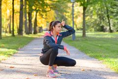 Woman wiping her brow with her hand. Woman wiping her brow with the back of her hand as she jogs outdoors in a park looking to the side Stock Images