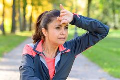 Woman wiping her brow with her hand. Woman wiping her brow with the back of her hand as she jogs outdoors in a park looking to the side Stock Photos