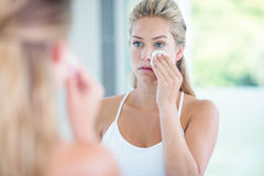 Woman wiping her face with cotton pad Stock Photography