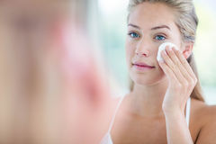 Woman wiping her face with cotton pad Royalty Free Stock Image