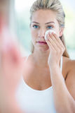 Woman wiping her face with cotton pad Stock Image