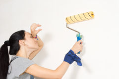 Woman wiping her forehead as she paints a wall Stock Image