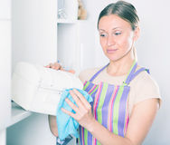 Woman wiping jewelry box. Woman in striped apron wiping dust on jewelry box at home Royalty Free Stock Photo