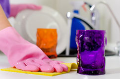 Woman wiping the kitchen counter top. With a dishcloth as she places the clean glasses and crockery from washing up on the surface stock photo