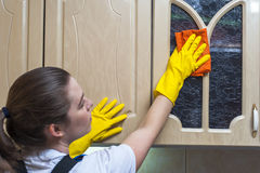 Woman wiping kitchen cupboard with rag Royalty Free Stock Photo