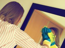 Woman is wiping mirror. House cleaning. Woman is wiping mirror in the room Royalty Free Stock Photos