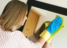 Woman is wiping mirror in the room. House cleaning. Woman is wiping mirror in the room Stock Photography