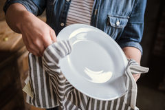 Woman wiping plate. Close-up partial view of woman wiping plate in kitchen Royalty Free Stock Photo