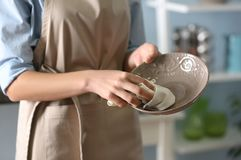 Woman wiping plate with napkin. At kitchen Royalty Free Stock Image