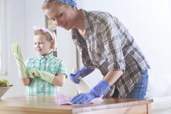 Woman wiping a table and her daughter helping her. Young women wiping a wooden table and her daughter helping her Royalty Free Stock Images